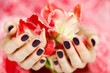 Cupped hands with dark manicure holding red flowers