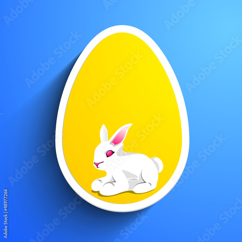 Little Easter Rabbit in the yellow Easter Egg on blue background