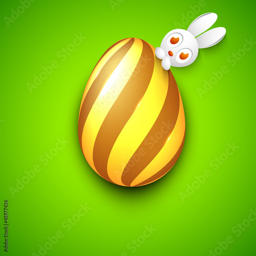 Cute Easter Bunny with golden Easter Egg on green background. EP