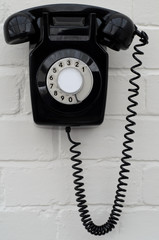 Black bakelite telephone on a brick wall