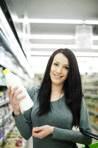 Woman choosing bottle of milk at supermarket