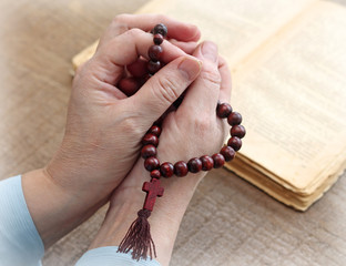 Woman's hands holding rosary, close-up