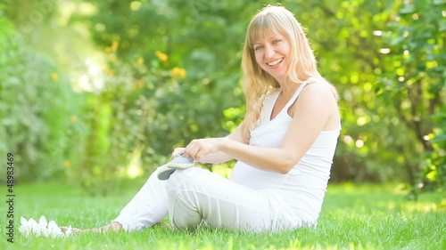 Happy  young pregnant woman playing with bootee in spring park