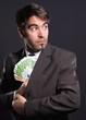 Mann im Anzug steckt Geldscheine ein