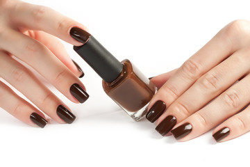 Hands with brown manicure and nail polish bottle isolated