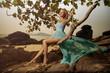 Beautiful Woman In Blue Fluttering Dress Swinging On A Beach Swi