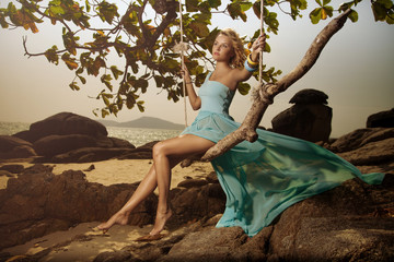 Beautiful Woman In Blue Fluttering Dress Swinging On A Beach Swi
