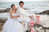couple of young man and woman in wedding suit ridiing old bicycl