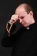 Young pastor with wooden rosary, isolated on black
