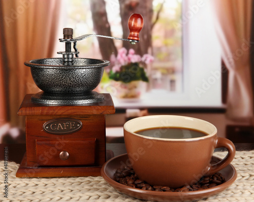 cup of coffee with scarf and coffee mill on table in room