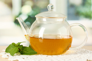 Teapot with mint on table in room
