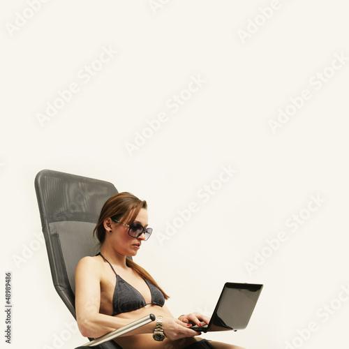 Frau im Bikini mit Laptop