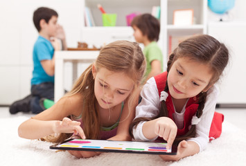 Little girls playing on a tablet computing device