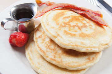 view of pancakes wit bacon, strawberry and syrup