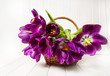 purple tulips in a basket on a white wooden table