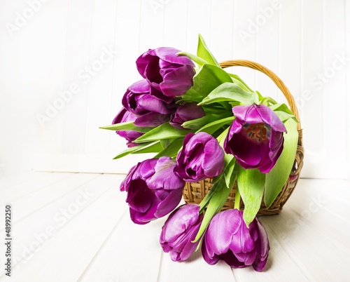 purple tulips in a basket on white wooden table