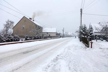 Wieś pokryta śniegiem w pochmurny dzień.