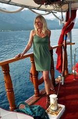 Junge, blonde Frau im Urlaub auf einem Schiff