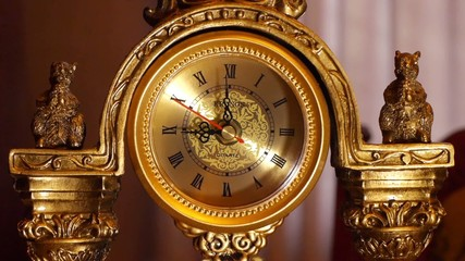 The arrows of the antique clock show 9:00.