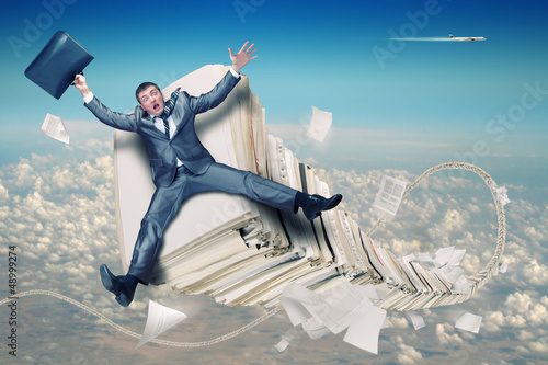 Businessman on stack of paperwork