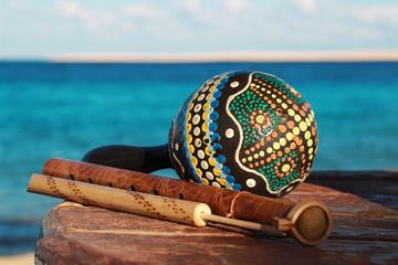 Музыкальные инструменты маракас, дудка и флейта на фон моря
