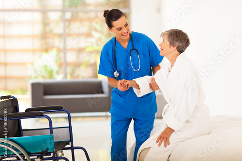 young female caregiver helping senior woman getting up