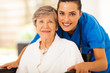 happy senior woman on wheelchair with caregiver - 49000494