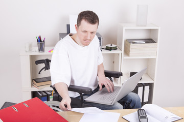 Man in wheelchair with laptop at work