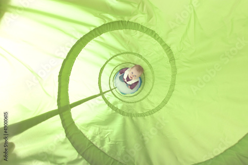 baby girl playing inside a toy tunnel