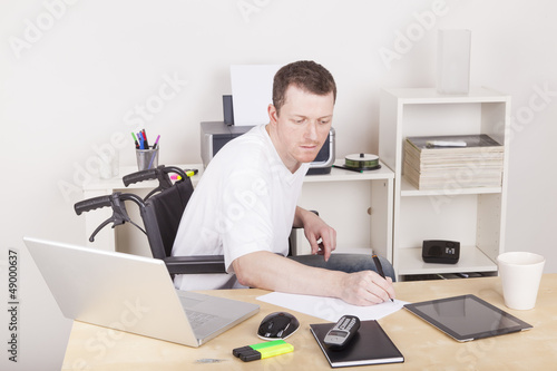 Man in wheelchair with tablet computer and laptop