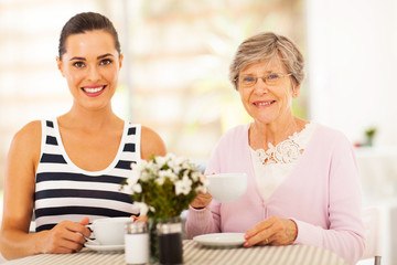 beautiful young woman having tea with grandmother or mother
