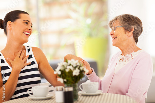 senior grandmother looking at granddaughter's new ring