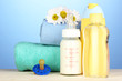 Baby bottle of milk, oil and shampoo near towels