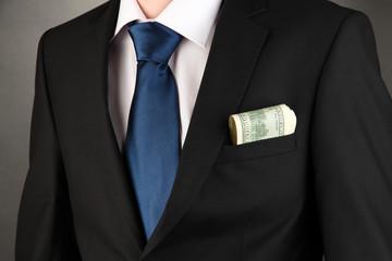Money in pocket of businessman on black background