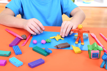 Child moulds from plasticine on table