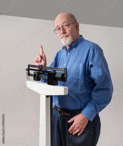 Senior Male on Weight Scale Holding Up One Finger