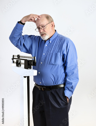 Senior Man on Weight Scale Looking Worried and Confused