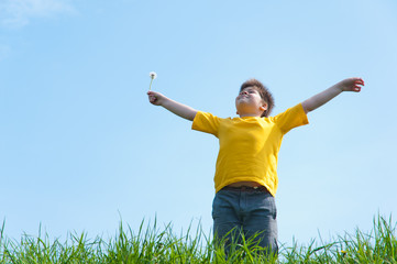 A boy stands on a green grass