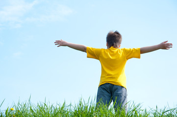 A boy stands on a green grass