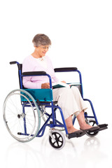senior woman sitting on wheelchair and reading a book