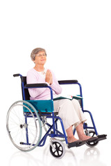 elderly woman sitting on wheelchair and praying