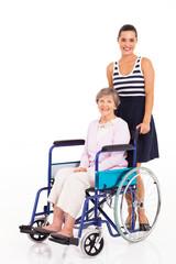 caring daughter pushing senior mother on wheelchair