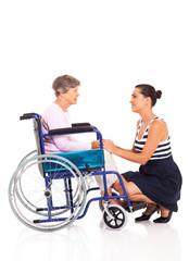 loving daughter talking to disabled senior mother