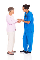 young female medical worker greeting senior woman