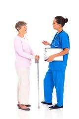 medical nurse talking to senior woman isolated on white