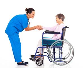 friendly nurse greeting disabled senior patient