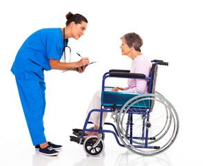 caring nurse helping senior patient filling medical form