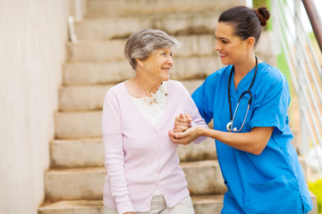 young caregiver helping senior woman walking down stairs