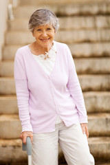 happy elderly lady standing by stairway with cane