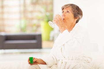 elderly woman drinking medicine at home